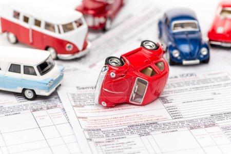 Photo pour Mise au point sélective des voitures jouets colorés sur les documents d'assurance - image libre de droit