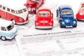 selective focus of colorful toy cars on insurance documents
