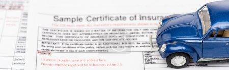 Photo pour Coup panoramique de voiture jouet bleu sur les documents d'assurance - image libre de droit