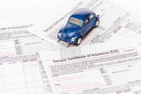Photo pour Voiture jouet bleu sur les documents d'assurance sur le blanc - image libre de droit