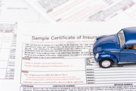 Photo pour Orientation sélective des documents d'assurance et de la voiture de jouet bleu - image libre de droit