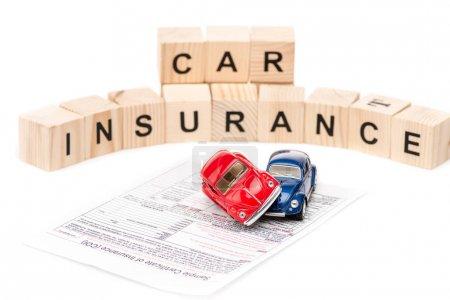 Photo pour L'accent sélectif des voitures de jouet, des blocs en bois avec des lettres et le certificat d'assurance isolés sur le blanc - image libre de droit