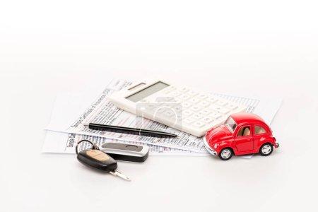 Photo pour Clés, calculatrice, certificats d'assurance et voiture jouet rouge sur surface blanche - image libre de droit