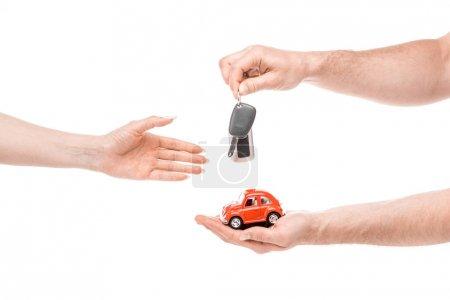 Photo pour Vue recadrée de l'homme donnant voiture jouet et clés à la femme isolée sur blanc - image libre de droit