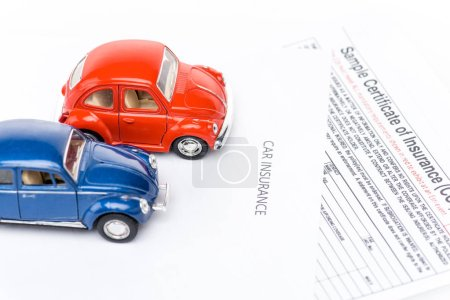 Photo for Red and blue toy cars on insurance certificates - Royalty Free Image