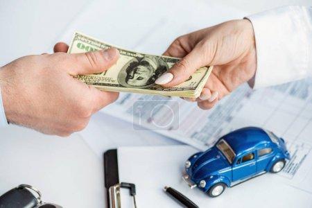 Foto de Vista recortada del hombre y la mujer que sostienen billetes de dólar cerca del coche de juguete, portapapeles y documentos - Imagen libre de derechos