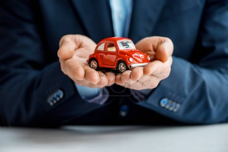 partial view of man in formal wear holding red toy car
