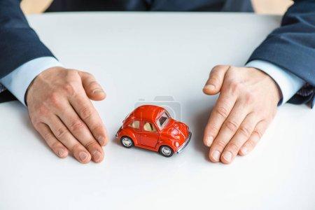 Photo pour Vue recadrée de l'homme dans l'usure formelle avec la voiture rouge de jouet - image libre de droit