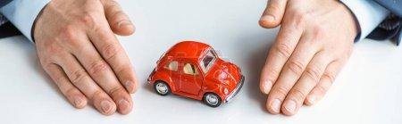 Photo pour Tir panoramique de l'homme dans l'usure formelle avec la voiture rouge de jouet - image libre de droit