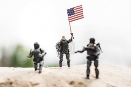 Photo pour Selective focus of toy soldier with weapon holding american flag on sand - image libre de droit