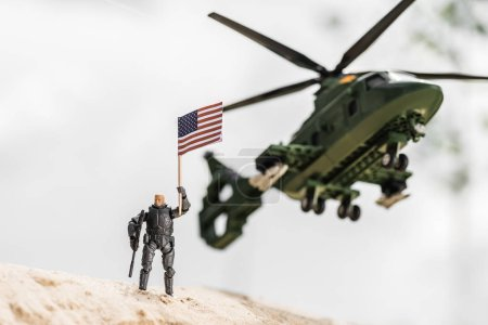 Photo pour Toy soldier holding american flag while standing on sand near helicopter - image libre de droit