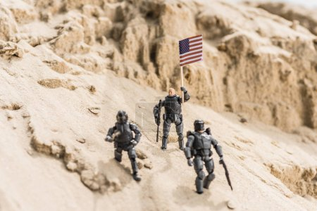 Photo pour Toy armed soldiers standing on sand and holding american flag - image libre de droit