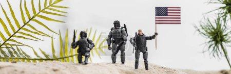 prise de vue panoramique de soldats jouets tenant le drapeau américain sur une dune de sable