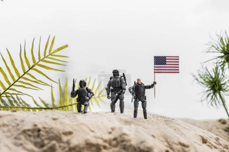 Photo for Selective focus of toy soldiers holding american flag on sand dune - Royalty Free Image