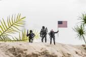 "Постер, картина, фотообои ""selective focus of toy soldiers holding american flag on sand dune"""
