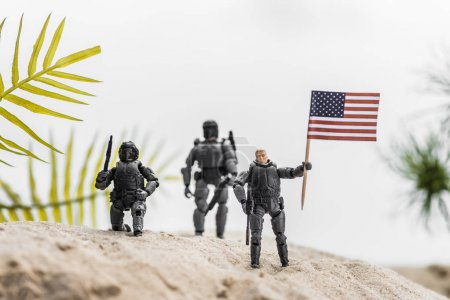 Photo for Selective focus of toy soldiers holding american flag on sand hill - Royalty Free Image
