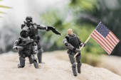 """Постер, картина, фотообои """"selective focus of toy soldiers aiming with guns at toy man with american flag on sand hill"""""""