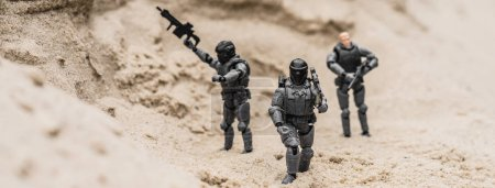 Photo for Selective focus of plastic toy soldiers on sand dune with guns, panoramic shot - Royalty Free Image