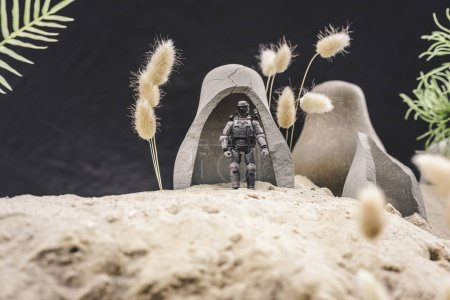 Photo for Selective focus of toy soldier with gun standing near caves on sand dune on black background - Royalty Free Image