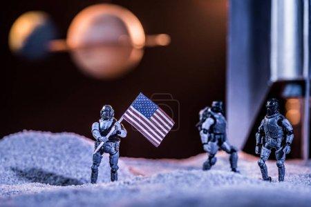 Photo pour Foyer sélectif des astronautes de jouet retenant le drapeau américain dans l'espace près de la fusée - image libre de droit