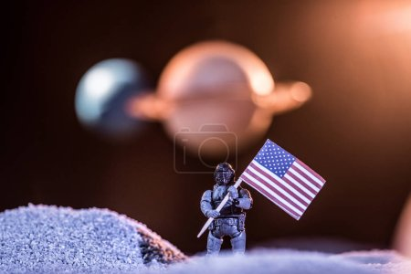 Photo pour Selective focus of toy astronaut holding american flag in space - image libre de droit
