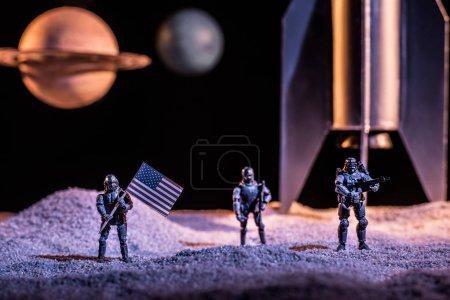 Photo pour Soldats de jouet retenant l'indicateur américain dans l'espace près de la fusée et des planètes - image libre de droit