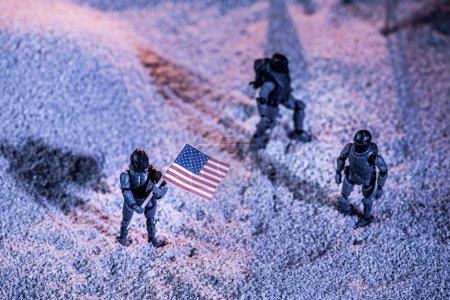 Photo for Overhead view of toy astronauts with american flag on cosmic planet - Royalty Free Image