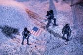 "Постер, картина, фотообои ""overhead view of toy astronauts with american flag on cosmic planet"""
