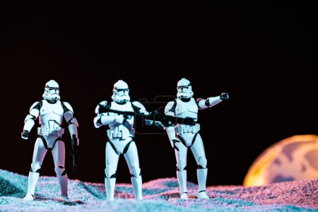 Photo pour KYIV, UKRAINE - MAY 25, 2019: white imperial stormtroopers with weapon on cosmic planet isolated on black - image libre de droit