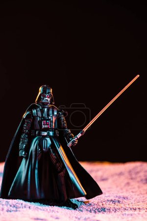 Photo for KYIV, UKRAINE - MAY 25, 2019: Darth Vader figurine with lightsaber isolated on black - Royalty Free Image