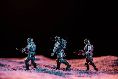 Photo for Toy soldiers walking with gun on planet in space isolated on black - Royalty Free Image