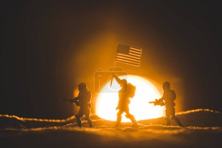 selective focus of toy soldiers silhouettes with guns and american flag walking on planet with sun on background