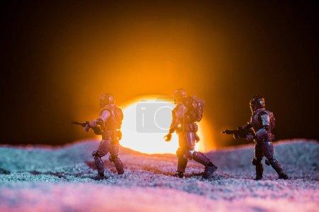 Photo pour Silhouettes de soldats de jouet avec des canons marchant sur la planète avec le soleil sur le fond - image libre de droit