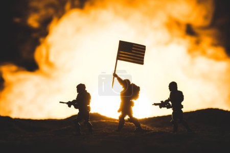 Photo pour Toy soldiers silhouettes with guns and american flag walking on planet with sun in smoke on background - image libre de droit