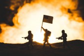 toy soldiers silhouettes with guns and american flag walking on planet with sun in smoke on background
