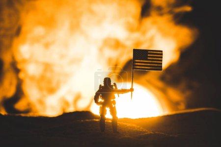 Photo pour Silhouette de soldat de jouet avec le drapeau américain sur la planète avec le soleil dans la fumée - image libre de droit