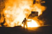 "Постер, картина, фотообои ""toy soldier silhouette with american flag on planet with sun in smoke """