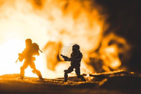 Photo pour Silhouettes de soldats de jouet avec des canons sur la planète avec le soleil dans la fumée sur le fond - image libre de droit