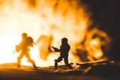 """Постер, картина, фотообои """"игрушки солдат силуэты с оружием на планете с солнцем в дыму на фоне"""""""