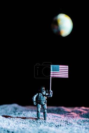 Photo pour Soldat de jouet retenant le drapeau américain national dans l'espace avec la planète Terre sur le fond noir - image libre de droit