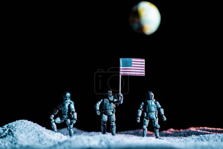 Photo pour Toy soldiers standing with usa flag on planet in space on black background with planet Earth - image libre de droit