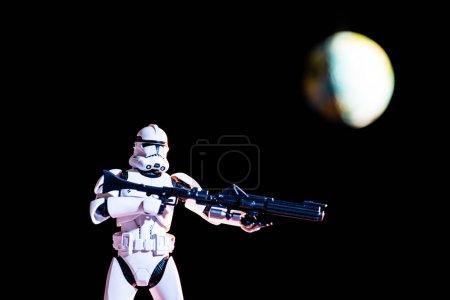Photo pour KYIV, UKRAINE - 25 MAI 2019 : chiffre de Stormtrooper impérial blanc avec pistolet sur fond noir avec planète Terre floue - image libre de droit