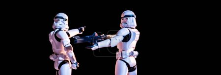 Photo pour KYIV, UKRAINE - MAY 25, 2019: white imperial stormtroopers with gun isolated on black - image libre de droit