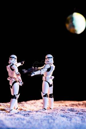 KYIV, UKRAINE - 25 MAI 2019 : Stormtrooper impérial blanc visant avec une arme à feu un autre sur fond noir avec la planète Terre