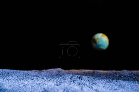 textured ground with blurred planet Earth in space isolated on black