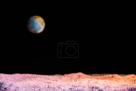 selective focus of textured ground with blurred planet Earth in space isolated on black
