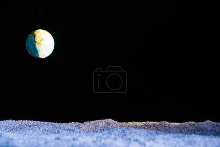 Foto de Sandy ground with blurred planet Earth in space isolated on black - Imagen libre de derechos