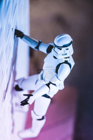 Photo for KYIV, UKRAINE - MAY 25, 2019: plastic Imperial Stormtrooper figurine climbing white textured wall - Royalty Free Image