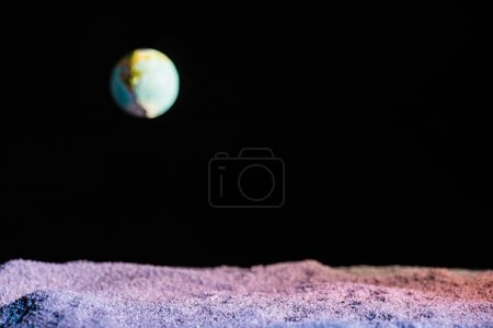 sandy ground with blurred planet Earth in space isolated on black with copy space