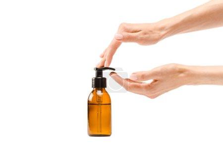 Photo pour Vue recadrée de la lotion de corps de pompage de femme de la bouteille de distributeur d'isolement sur le blanc - image libre de droit